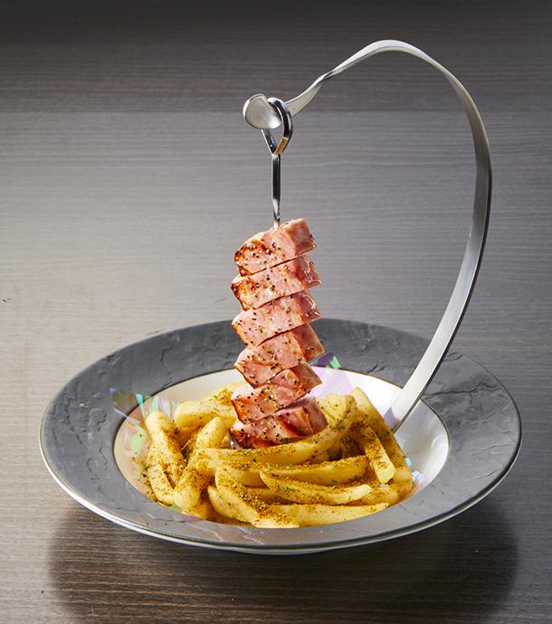 ロボ基地 セントラルタワー(税込1058円)。厚切りベーコンを串に刺し、タワー風に盛り付けます。 付け合せのポテトはパクチー風味
