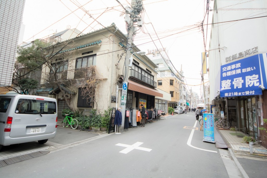 ▲右に青い接骨院がある十字路を左に曲がって数mで右手に建物がある。