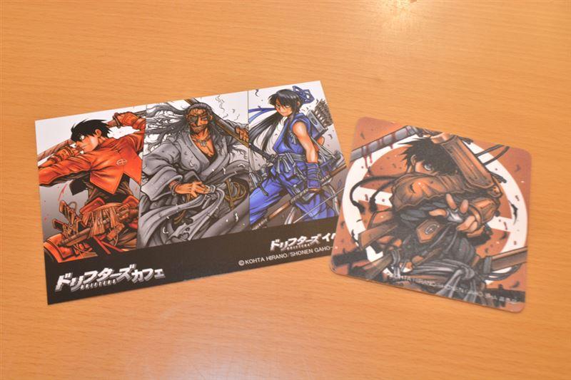 ▲入店時に貰えるポストカード(左)と、ドリンク注文で貰えるコースター(左)。ポストカードの裏面は描き下ろし絵柄となっている。