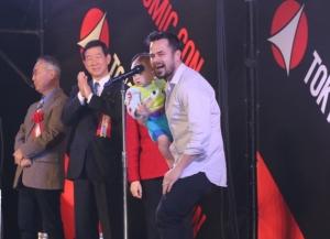 子供を抱いて登壇した第1回東京コミコン親善大使の俳優ダニエル・ローガン
