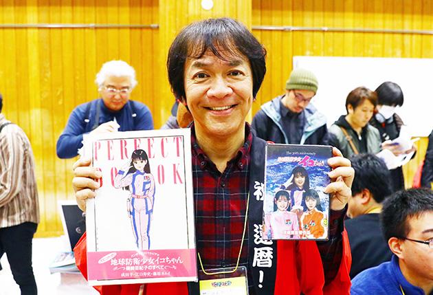 河崎実監督。ご自身のプロデビュー作である『地球防衛少女イコちゃん』のDVDとパーフェクトブックを持ち笑顔